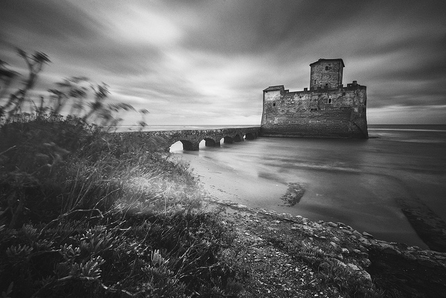 Long exposure of an abandoned fortress by a beach. There is a brighter area over the foliage on the left, caused by a light leak through the camera's viewfinder.