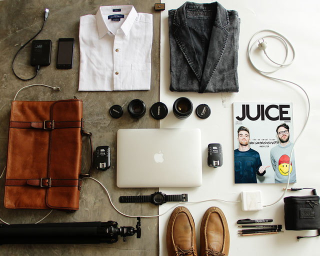 Flat lay photo of camera equipment and clothes equally spread across the left and right halves of the image to create a balanced photo.