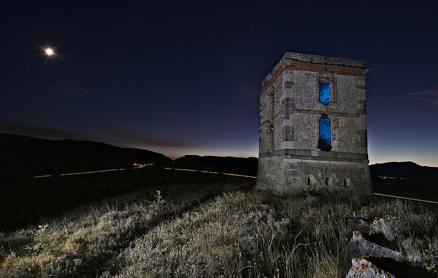 Landscape photo of a tower taken at night. The outside of the tower was painted with a bright white light, and the inside was painted with blue light.