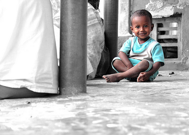 Selective color photo of a young pilgrim resting on thinnai
