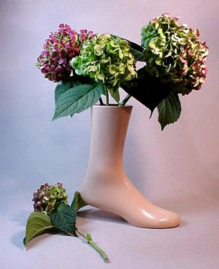 Foot shaped vase filled with flowers