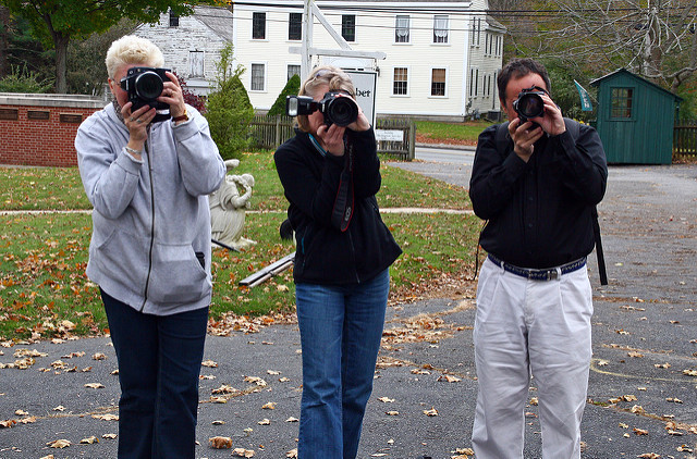 3 people demonstrating the right way to hold a camera for maximum stability