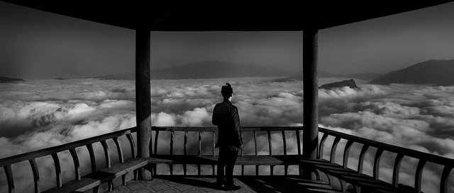 Man standing in pagoda overlooking a sea of clouds, taken as part of a photography challenge