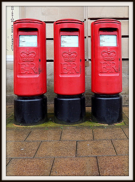 3 red British post boxes, taking up the majority of the frame