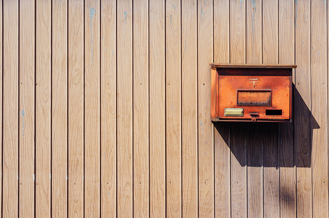 Photo of a rusty Japanese mail box where the mail box only takes up a small portion of the frame