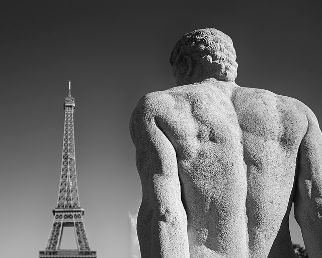 Large statue looking at small Eiffel Tower