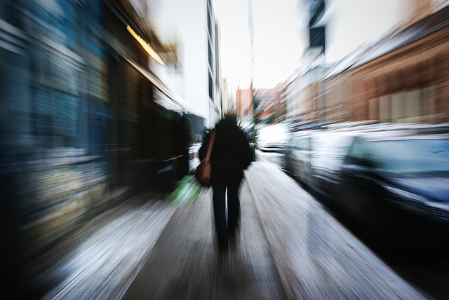 zoom blur photo of a person walking along a street