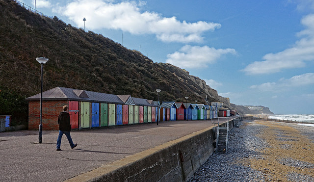Row of beach huts along the top of a beach. The decreasing size of the beach huts (in terms of how much of the image they take up) works to indicate depth within the image.