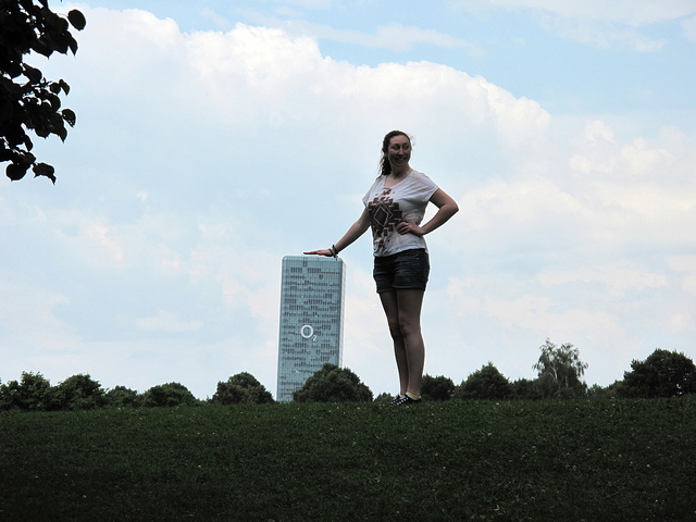 Forced perspective photo of what appears to be a giant resting her hand on a tower block