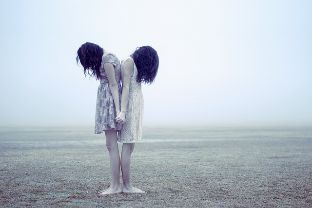 Conceptual portrait of two girls standing back to back in a field on a misty day. Due to the mist the lighting is very soft and non-directional, resulting in a low contrast image.
