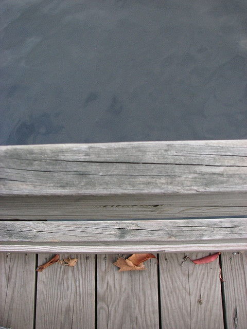 Close-up of the edge of a wooden walkway over water, abstracted into shapes