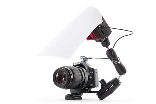 Camera with macro flash bracket and small 2-battery flash mounted on the bracket, with bent white bounce card attached to the flash.
