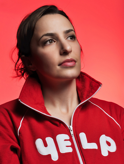 Portrait of woman wearing a red top against a red background. The subject was lit with a flash fired by radio trigger, while the background was lit by a gelled flash fired by its built-in optical trigger