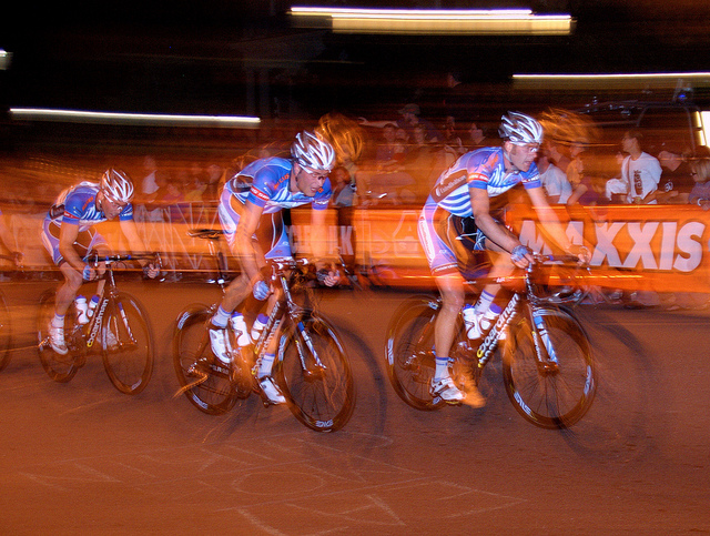Men's Cycle race, photographed using a slow shutter speed and first curtain flash. The riders almost appear to be going backwards as their blurred outlines stretch in front of them.