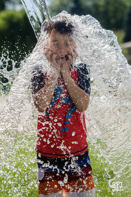 High speed photo of a boy being splashed with water, taken outdoors on a sunny day and using high speed sync flash