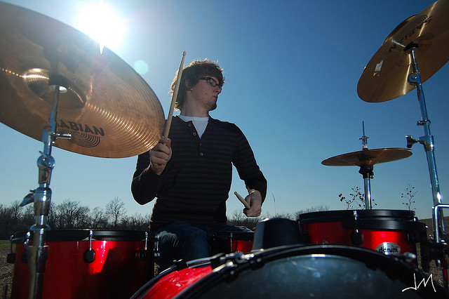 Drummer outdoors in sunshine, underexposed for the ambient light and lit with high speed sync flash